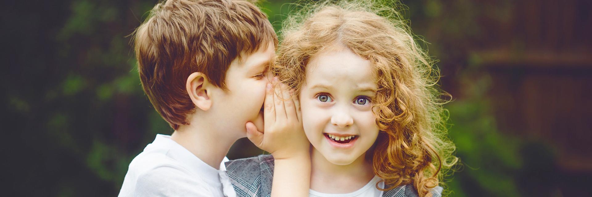 Zwei Kinder erzählen sich ein Geheimnis